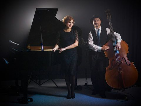 Solo pianist Yuliya Drogalova is standing in front of a black grand piano, next to her is double bassist Bartek Mlejnek